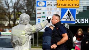 رجل يخضع لفحص درجة الحرارة على نقطة عبور الحدود بين بولندا وألمانيا، 15 مارس/ آذار 2020