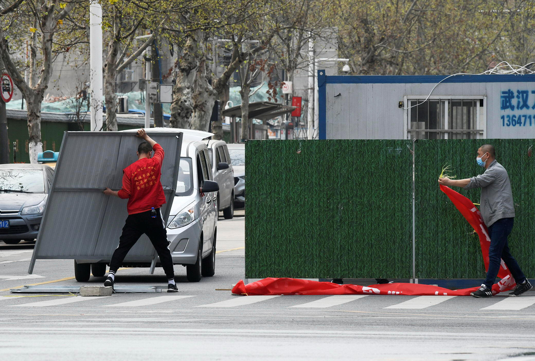 Workers wearing face masks remove barriers on a street in Wuhan, the epicentre of the novel coronavirus disease (COVID-19) outbreak, as the city has started to loosen its lockdown, in Hubei province, China March 21, 2020. Picture taken March 21, 2020. China Daily via REUTERS ATTENTION EDITORS - THIS IMAGE WAS PROVIDED BY A THIRD PARTY. CHINA OUT.