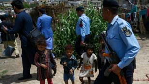Des policiers encadrent des membres d'équipes de vaccination anti-polio le 26 avril 2019, dans la banlieue d'Islamabad.