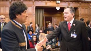 El presidente boliviano, Evo Morales, estrecha la mano de Roberto Ampuero, ministro de Relaciones Exteriores de Chile, mientras llega para la apertura de audiencias en el Tribunal Internacional de La Haya, Holanda, el 19 de marzo de 2018.
