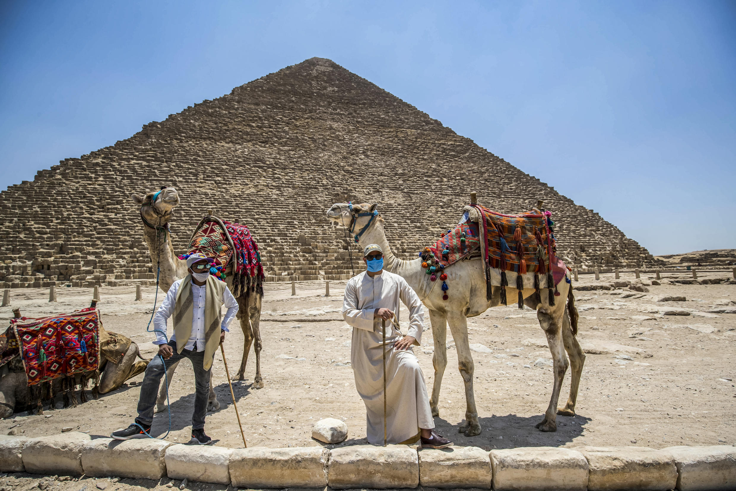 Mask-clad camel guides stand by their camels near the Great Pyramid of Khufu (Cheops) at the Giza Pyramids necropolis on the southwestern outskirts of the Egyptian capital Cairo on July 1, 2020.