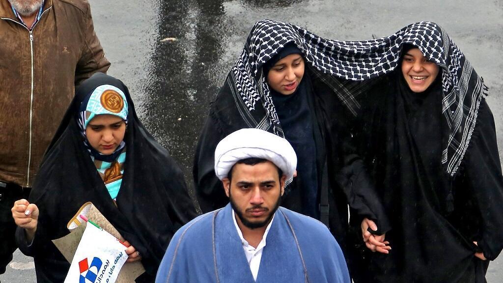Las mujeres iraníes marchan bajo la lluvia durante una ceremonia que celebra el 40 aniversario de la Revolución Islámica en la capital, Teherán, el 11 de febrero de 2019.
