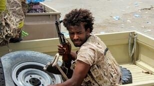 """A Yemeni fighter from the Amalqa (""""Giants"""") Brigades, loyal to the Saudi-backed government, rides in the back of a pickup truck during the offensive to seize the Red Sea port city of Hodeida from Iran-backed Huthi rebels in June 2018"""