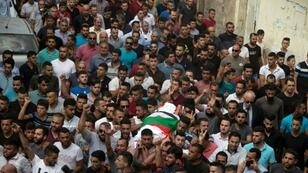 Palestinians carry the body of Aisha Rabi, who was killed when stones were thrown at the car she was travelling in, on October 13, 2018