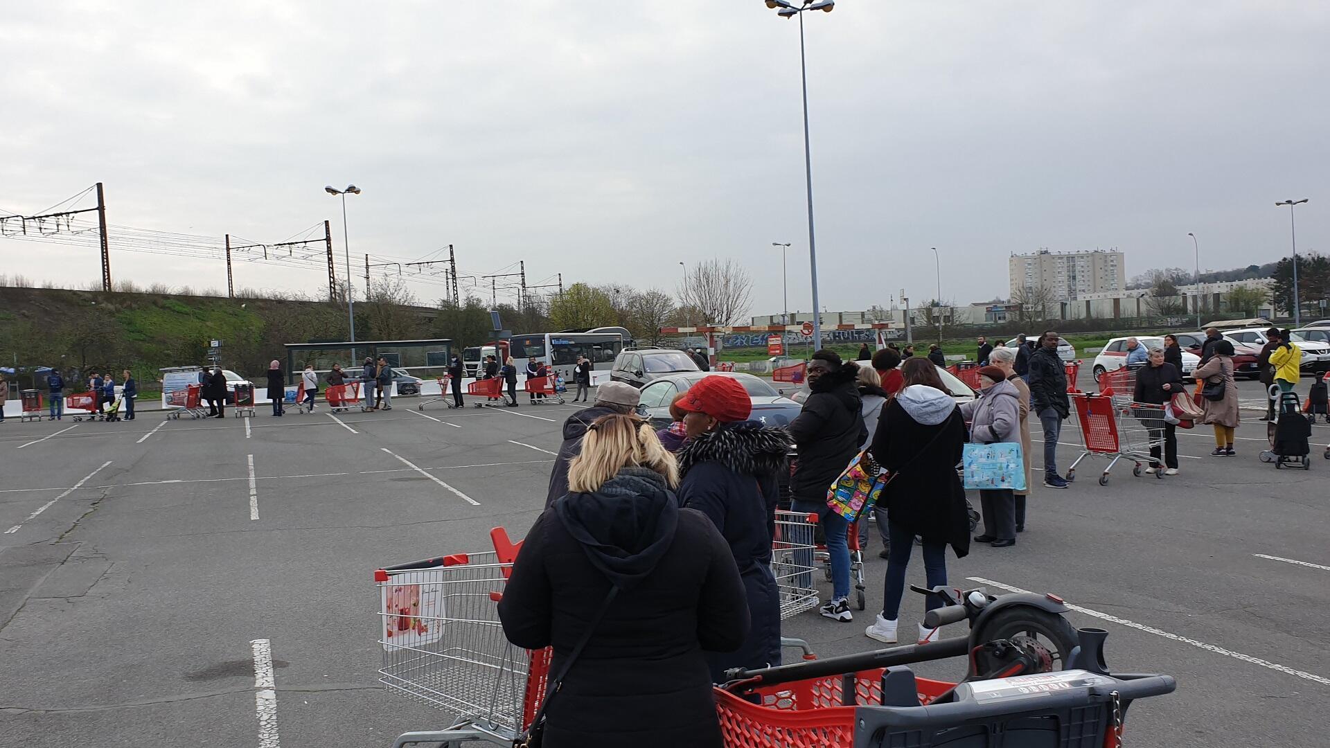 فرنسيون يصطفون أمام أحد المتاجر لتخزين احتياجاتهم قبل بدء سريان الحجر الصحي.