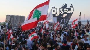 Manifestantes libaneses se reúnen para encender la 'antorcha del 17 de octubre' que marca el primer aniversario del inicio de un movimiento de protesta antigubernamental a nivel nacional, frente al devastado puerto de la capital, Beirut, donde en agosto tuvo lugar una explosión masiva.