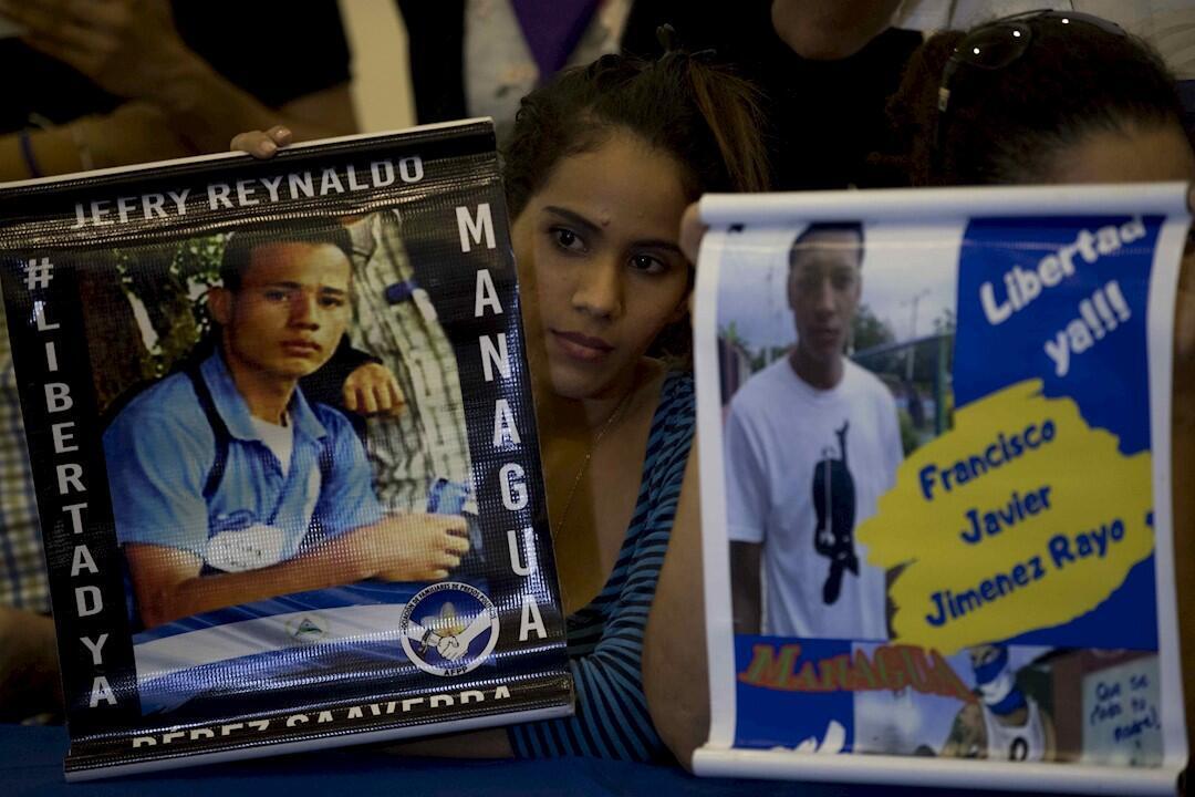 """Una joven sostiene un cartel con la imagen de un joven """"preso político"""", durante una conferencia de la Unidad Nacional Azul y Blanco (UNAB), en Managua, Nicaragua, el 18 de noviembre 2019."""