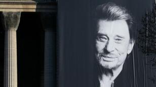 Un afiche gigante del fallecido cantante francés Johnny Hallyday se exhibe en la fachada de la Iglesia de la Madeleine en París, Francia, durante un tributo popular a esta mítica figura de la música y la cultura popular francesa.