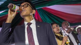 """Le président malgache Andry Rajoelina boit un remède """"Covid Organics"""" lors d'une cérémonie de lancement à Antananarivo le 20 avril 2020"""