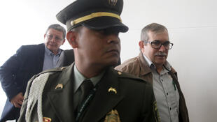 Former rebel leaders Rodrigo Londono, back right, and Pablo Catatumbo, back left, walk past a police officer after holding a press conference after they appeared before a special peace tribunal to testify in an ongoing probe of their role in civilian kidnappings in Bogota, Colombia, on September 23, 2019.