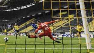 Le défenseur de Dortmund, Raphael Guerreiro (d), marque son second but contre Schalke lors du premier match de reprise de la Bundesliga, à Dortmund, le 16 mai 2020