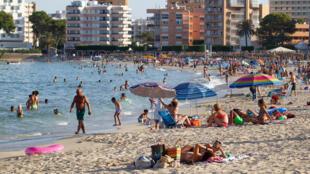Los turistas disfrutan del mar y la arena en la playa de Palmanova, el 27 de julio de 2020 en la ciudad española de Palma de Mallorca, capital de las islas Baleares