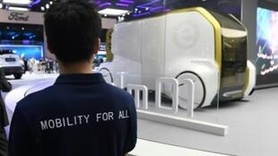 This photo taken on April 17, 2019 shows a Toyota staff member looking at a Toyota e-Calm 01 autonomous vehicle at the Shanghai Auto Show in Shanghai.Global automakers are positioning for a brave new world of on-demand transport that will require a car of the future -- hyper-connected, autonomous, and shared -- and China may become the concept's laboratory.