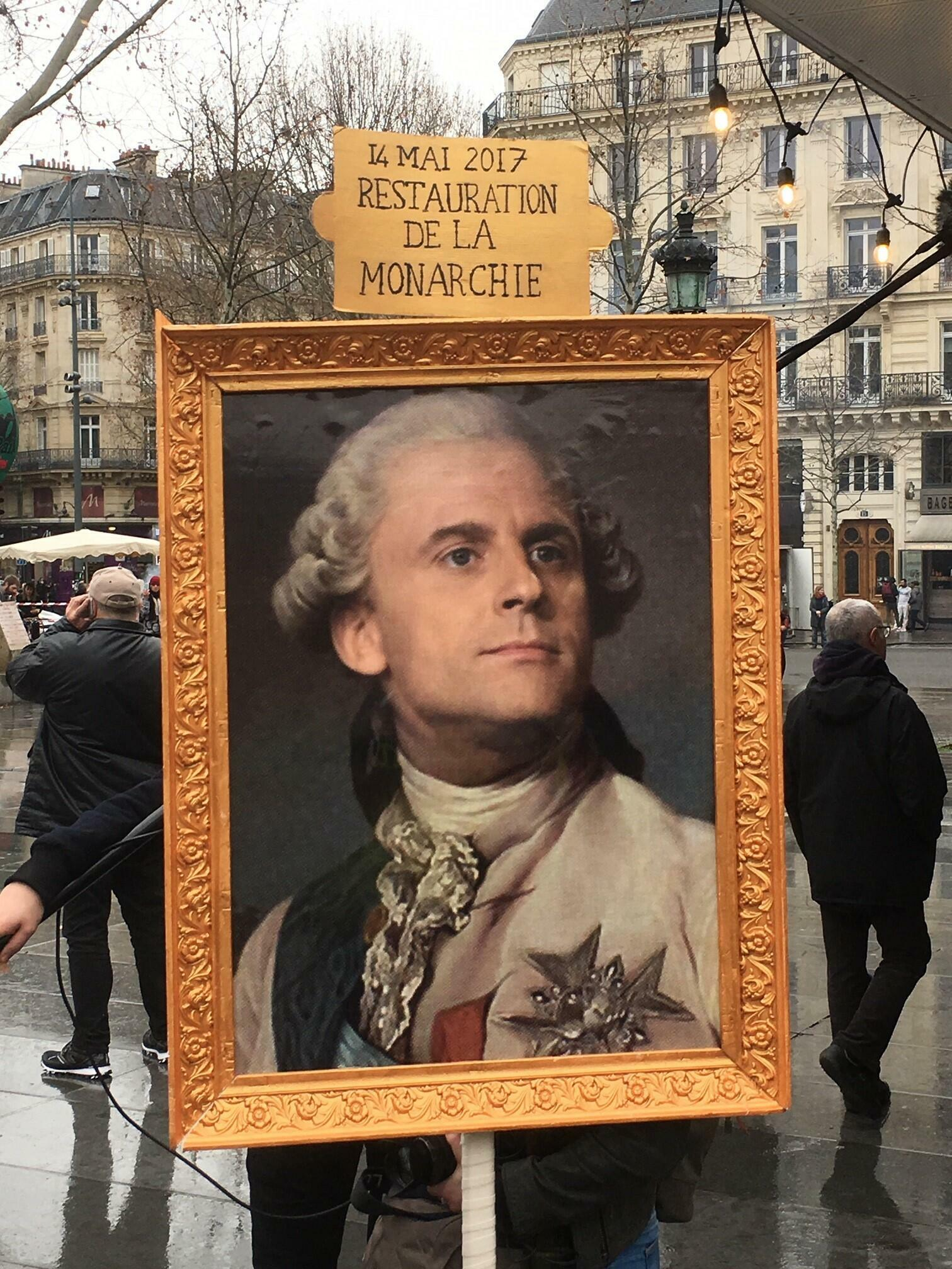 "Many protesters view Macron as remote and regal. Here his tenure is styled as ""the restoration of the monarchy""."