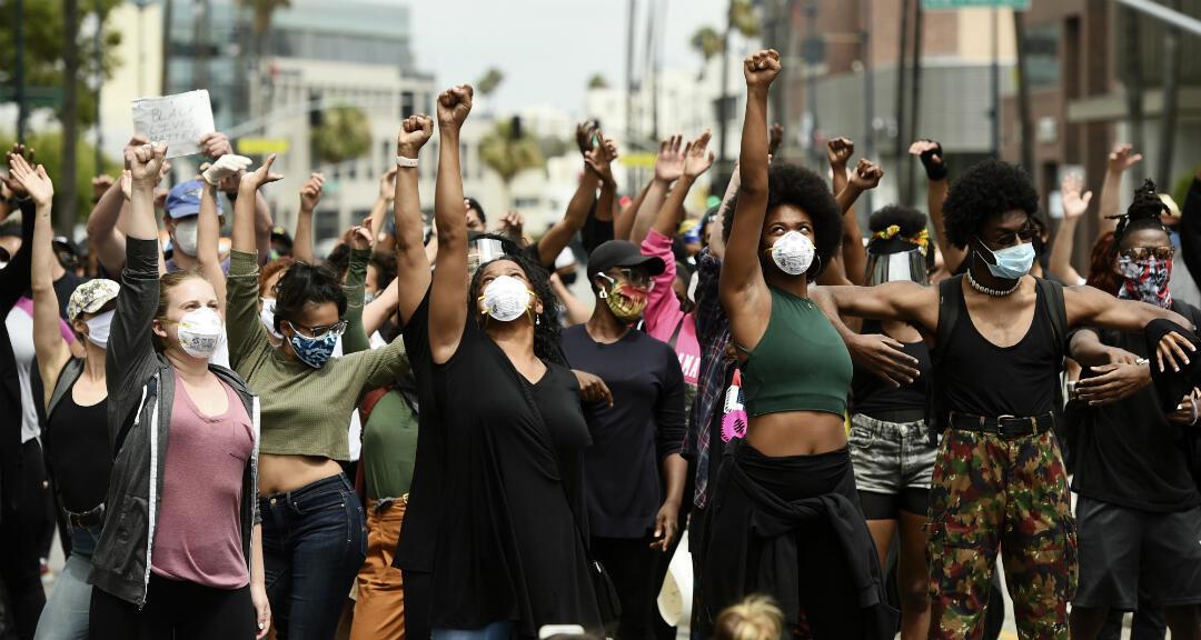 El 5 de junio de 2020 manifestantes alzan sus puños durante una manifestación en apoyo del movimiento 'Black Lives Matter' fuera de la Academia de Artes y Ciencias Cinematográficas en Beverly Hills, California.
