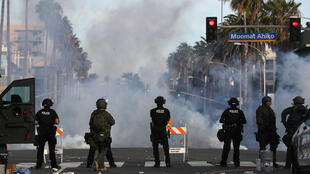 California police watch as tear gas is deployed during demonstrations in Santa Monica on May 31, 2020, in the aftermath of George Floyd's death.