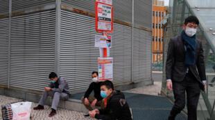 Des hommes portant un masque de protection attendent un bus à Macau, le 5 février 2020.