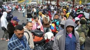Venezuelan citizens wait in line to cross into Ecuador on August 11, 2018, as millions of Venezuelans flee their country due to lack of resources such as food and medical supplies