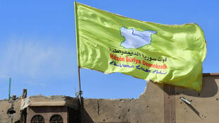Los combatientes de las Fuerzas Democráticas Sirias (FDS), respaldadas por Estados Unidos, plantaron su bandera en lo alto de un edificio en el último bastión del grupo Estado Islámico en Baghuz, en el este de Siria, después de declarar derrotado al grupo yihadista, el 23 de marzo de 2019.