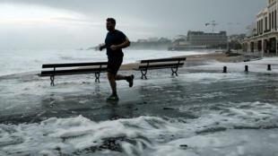 Un homme court le long de la Grande Plage de Biarritz, dimanche 3 novembre 2019, alors qu'une tempête s'est abattue sur la côte Atlantique.