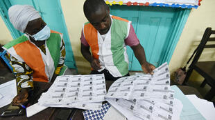 Workers of the Independent Electoral Commission (IEC) count the number of voters after the closure of the polling stations in Abidjan, Ivory Coast, on March 6, 2021.