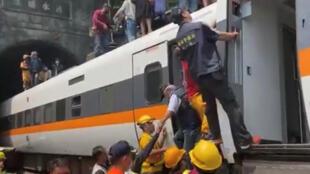 Des sauveteurs portent secours à des passagers du train, le 2 avril 2021, près de la ville côtière de Hualien, à Taïwan.