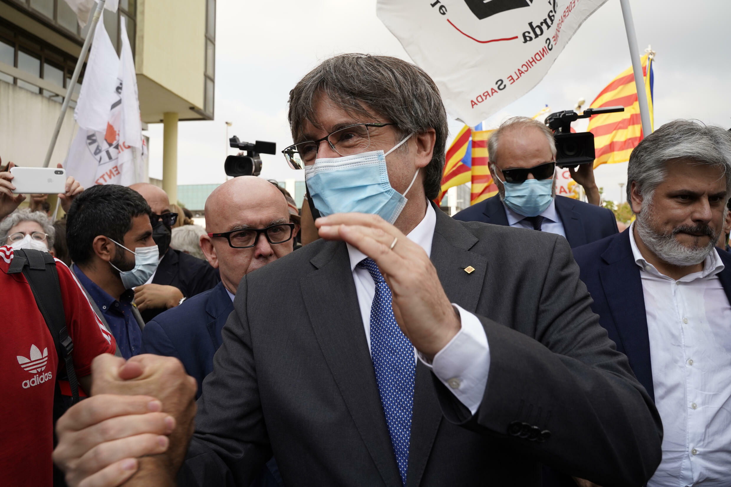 Puigdemont greets supporters outside the Sassari courthouse after his extradition hearing