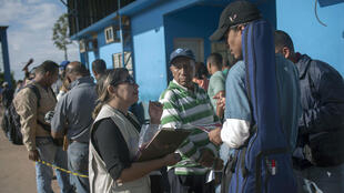 Una trabajadora brasileña del servicio de Vigilancia Sanitaria conversa con los venezolanos que esperan en fila delante de la Oficina Federal de Policía de Brasil, en la frontera entre Venezuela y Brasil en Roraima, Brasil, el 28 de febrero de 2018.