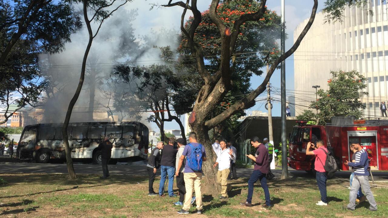 Des passants regardent un bus incendié pendant la grève générale contre la réforme des retraites, à São Paulo, le 14 juin 2019.