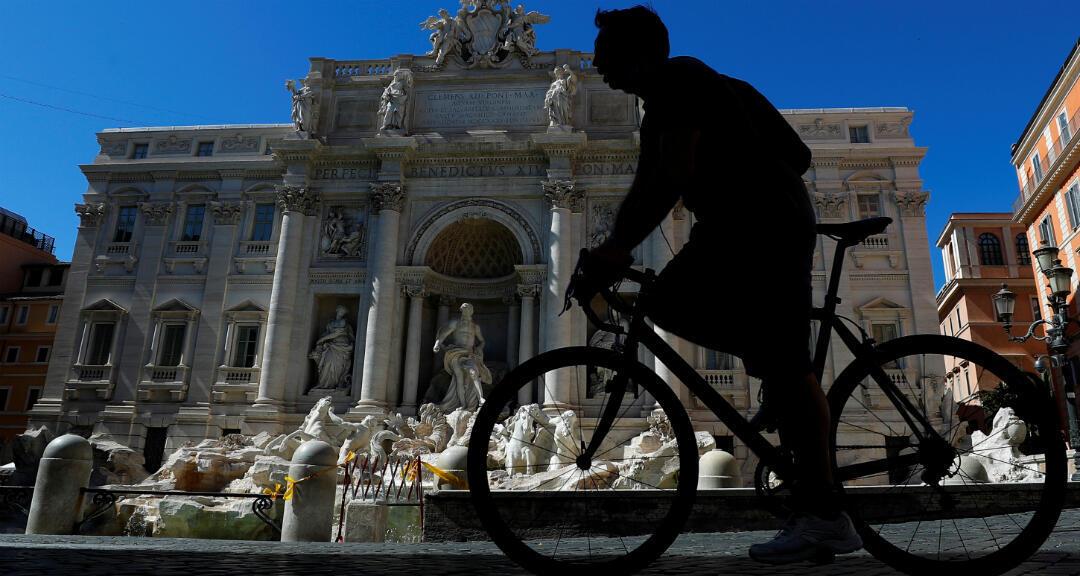 Un ciclista pasa por la Fontana de Trevi, mientras Italia comienza a aliviar algunas de las restricciones de la cuarentena. Roma, Italia, el 7 de mayo de 2020.