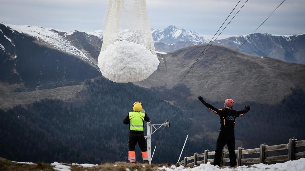 A helicopter transports snow to the lower slopes of the Luchon-Superbagnères ski resort in southwestern France on February 15, 2020. © AFP - Anne-Christine Poujoulat