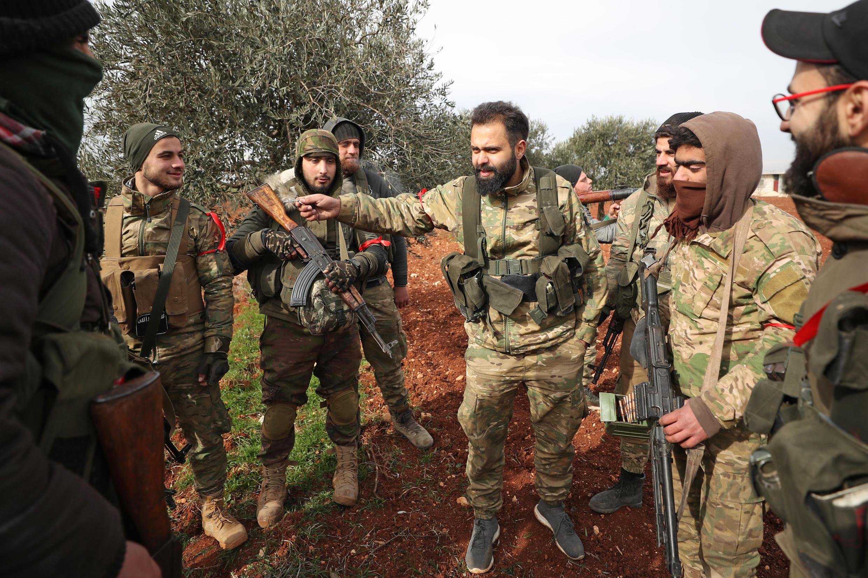 Combatientes sirios respaldados por Turquía se reúnen en la ciudad de Sarmin, a unos 8 kilómetros al sureste de la ciudad de Idlib, en el noroeste de Siria, el 11 de febrero de 2020.
