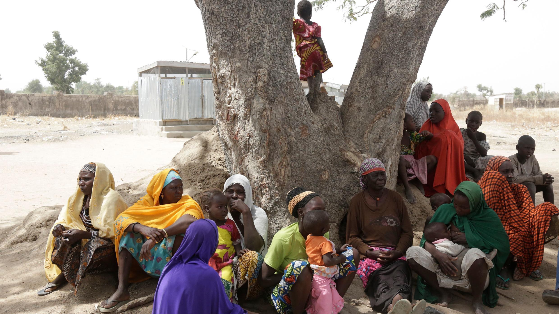 En esta foto tomada el lunes 18 de febrero de 2019, mujeres y niños desplazados por extremistas islamistas se sientan debajo de un árbol en el campamento de Malkohi en Yola, Nigeria.
