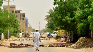 """Des résidents soudanais marchent près de barricades à Khartoum, le 9 juin 2019, lors du premier jour de """"désobéissance civile"""" lance par le mouvement de contestation."""
