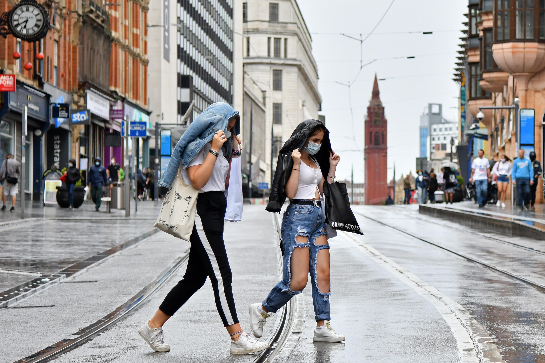 Deux jeunes femmes masquées sous la pluie de Birmingham, dans le centre de l'Angleterre, le 22 août.
