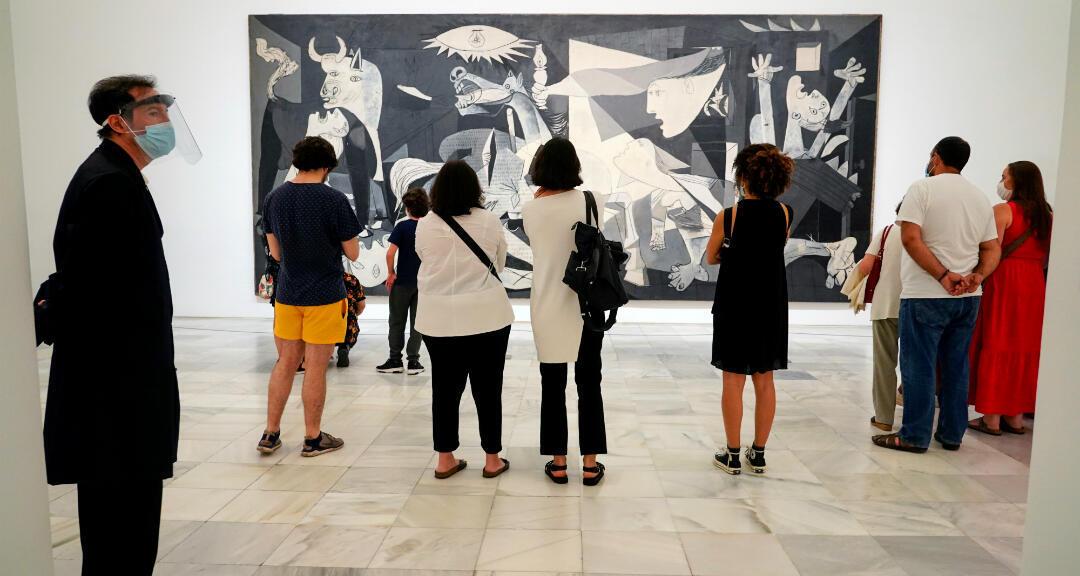 Visitantes miran el cuadro de Pablo Picasso 'Guernica' durante la reapertura del museo Reina Sofía. Madrid, España, 6 de junio de 2020.