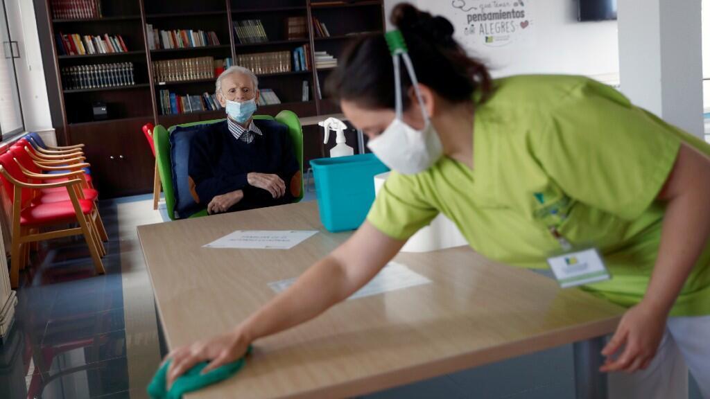 Un residente espera que una trabajadora del centro para adultos mayores desinfecte la mesa donde ha tenido visitas. En Navalcarnero, Madrid, España. 8 de junio de 2020.