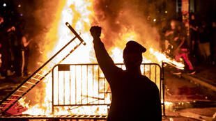 A protester raises a fist near a fire during a demonstration outside the White House over the death of George Floyd on May 31, 2020.