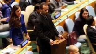Un membre de l'ONU dépose son bulletin de vote, jeudi 16 octobre
