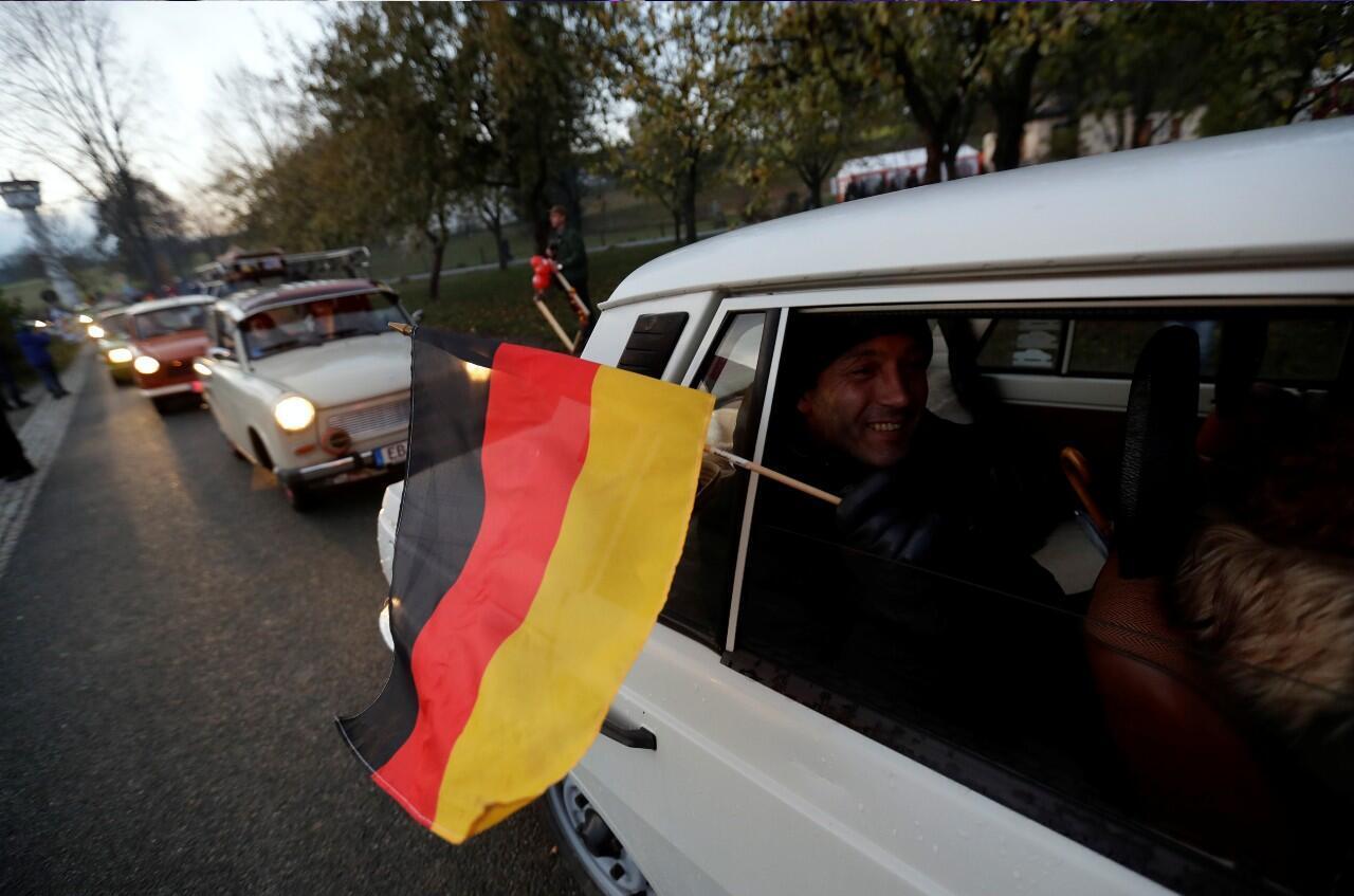 Varios automóviles durante un desfile que conmemoró el 30 aniversario de la caída del Muro de Berlín en un antiguo cruce fronterizo entre el este y el oeste de Alemania en la antigua aldea fronteriza de Moedlareuth, Alemania, el 9 de noviembre de 2019.