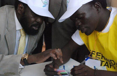 November 2010. Southern Sudan President Salva Kiir (left) registers to vote for the January 9, 2011 referendum at the grave site of the former rebel leader and the south's first president, John Garang. ©AFP
