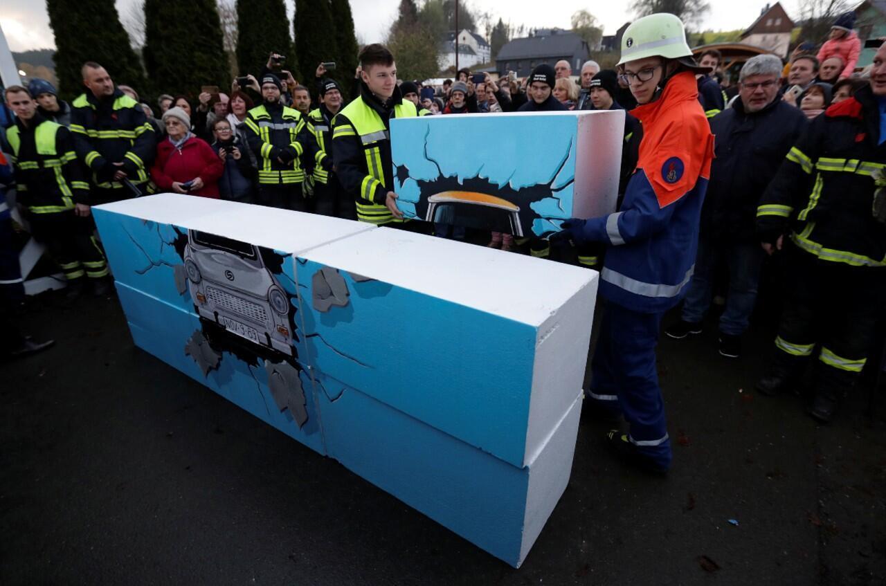 Un grupo de bomberos mientras desmontaba unos bloques de una pared que representa un automóvil Trabant rompiéndolo durante un desfile que conmemoró el 30 aniversario de la caída del Muro de Berlín en Moedlareuth, Alemania, el 9 de noviembre.