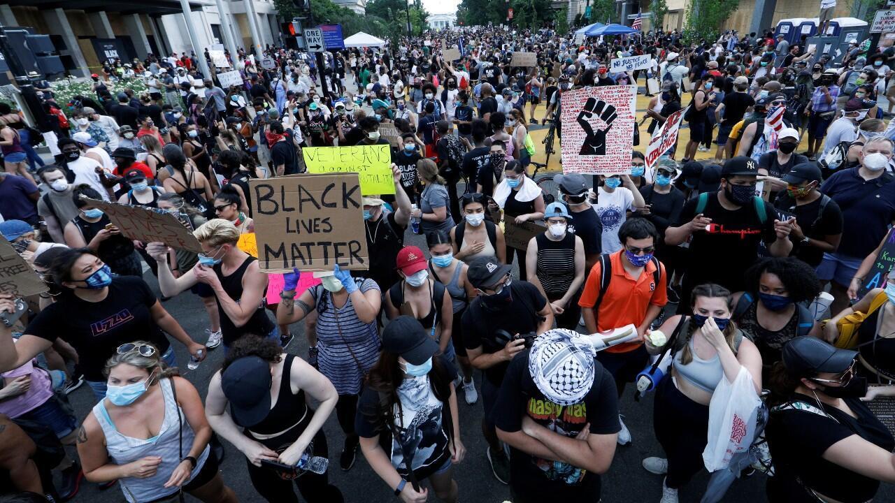 """Manifestantes sostienen pancartas mientras se reúnen bajo el grito de """"Black Lives Matter"""", cerca de la Casa Blanca, durante una protesta contra la desigualdad racial después de la muerte bajo custodia policial de George Floyd en Minneapolis. En Washington, Estados Unidos, el 6 de junio de 2020."""