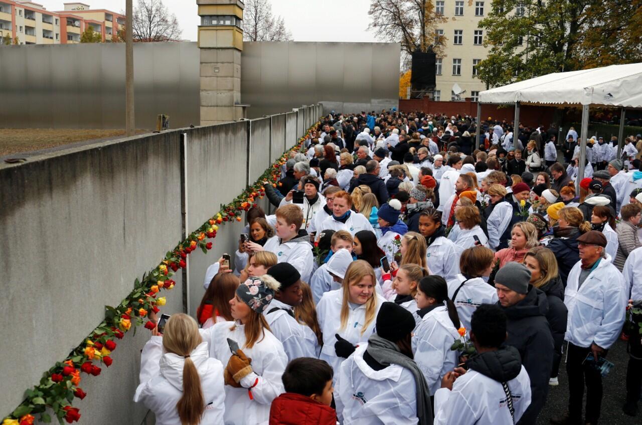 Un grupo de personas colocan rosas en el memorial durante una ceremonia que conmemoró el 30 aniversario de la caída del Muro de Berlín en Bernauer Strasse, Alemania, el 9 de noviembre de 2019.