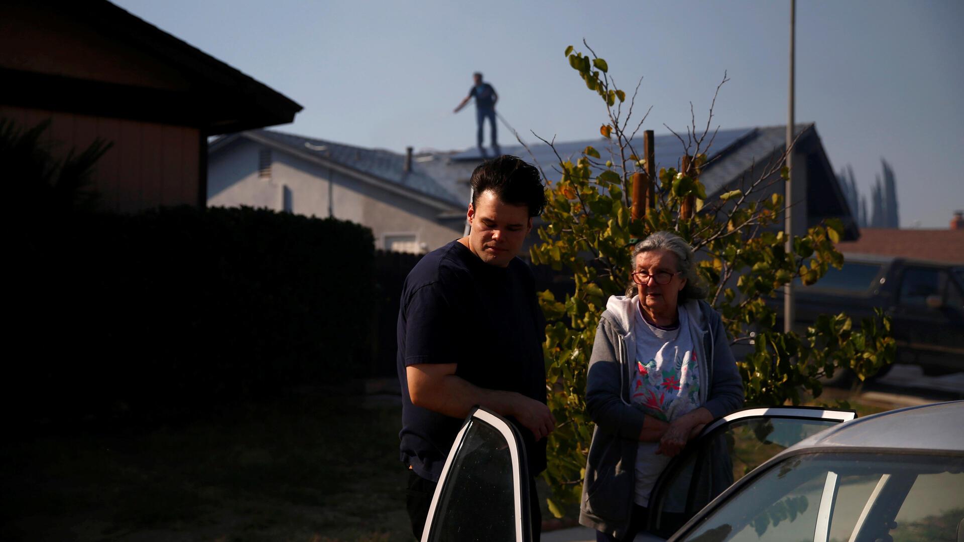 Residentes son fotografiados en Simi Valley, California, mientras los bomberos sofocan las llamas, cada vez más cerca de sus casas.