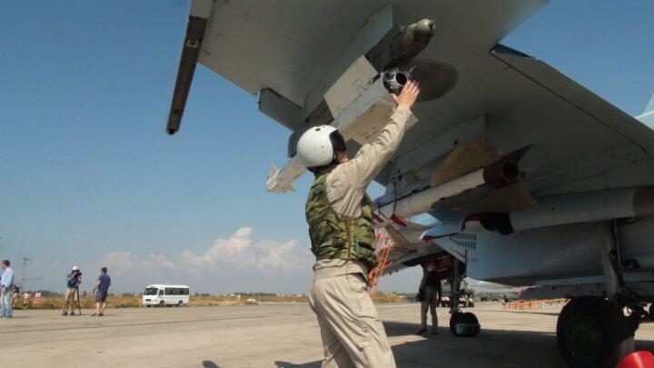 Des pilotes et techniciens russes inspectent un avion de chasse russe, le 5 octobre 2015 sur la base syrienne de Hmeimim.