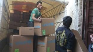 سوريون يفرغون في 28 نوفمبر 2017 مساعدات إنسانية قرب مدينة النشابية بمنطقة الغوطة الشرقية قرب دمشق الخاضعة للفصائل المعارضة المسلحة
