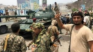 انفصاليون جنوبيون أمام دبابة استولوا عليها من قاعدة عسكرية في جنوب مدينة عدن اليمنية في 10 آب/أغسطس 2019