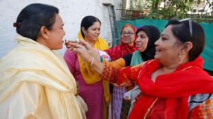 """Activistas ofrecen dulces para celebrar un proyecto de ley en el parlamento para enjuiciar a los hombres musulmanes que se divorcian de sus esposas mediante el """"triple talaq"""" o divorcio instantáneo en Ahmedabad, India, el 28 de diciembre de 2017."""