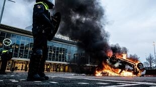 A car burns after being set on fire in front of the train station in Eindhoven, Netherlands, on January 24, 2021, after several hundred people protested against the country's new Covid-19 curfew.